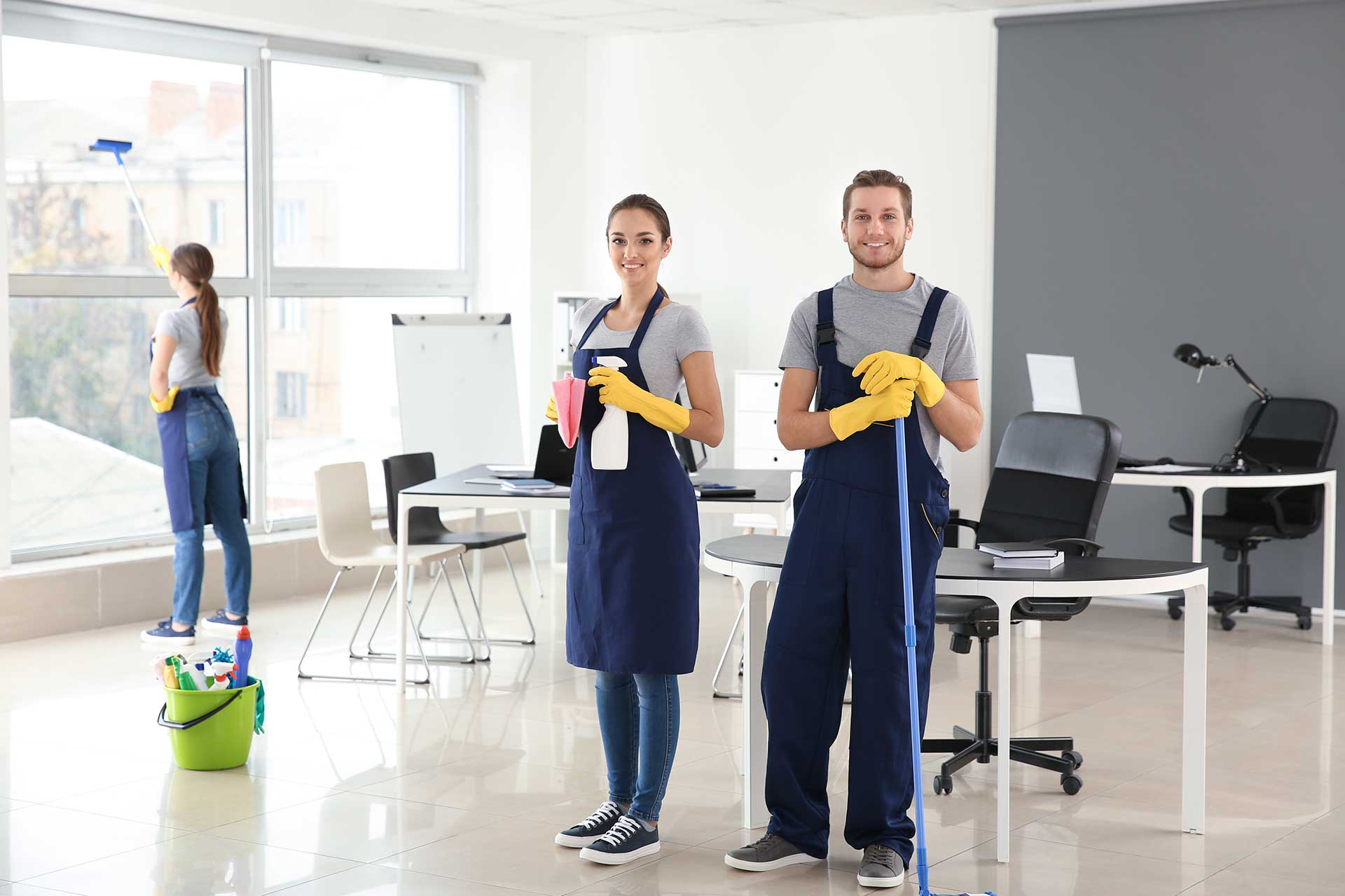 A picture of two women and one man cleaning an office